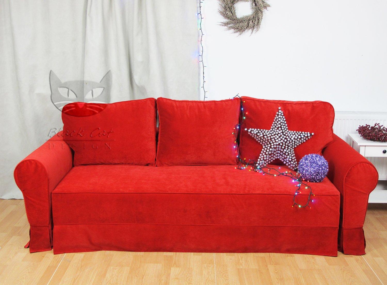 Szara kanapa z gałęziami świerku w tle